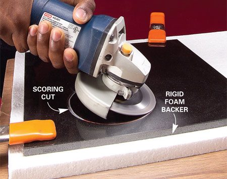 <b>Photo 1: Score the circle</b></br> Score the front of the tile along the circle guideline with the diamond blade. Tilt the grinder about 30 degrees and cut about 1/16 in. deep.