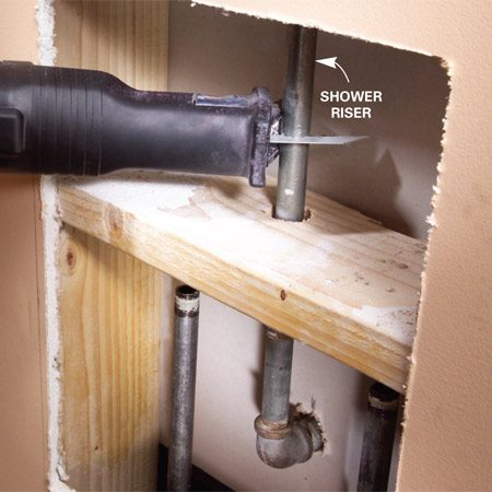 <b>Photo 2: Cut the shower riser</b></br> <p>Cut the shower riser with a reciprocating saw or jigsaw. Cut slowly and gently so you don't loosen the connections above.</p>