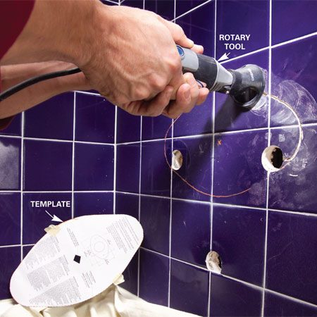 <b>Photo 1: Cut the tile</b></br> <p>Cut a hole for the new valve using a rotary tool equipped with a tile-cutting bit. Mark the cutout using the cover's paper template and a crayon.</p>