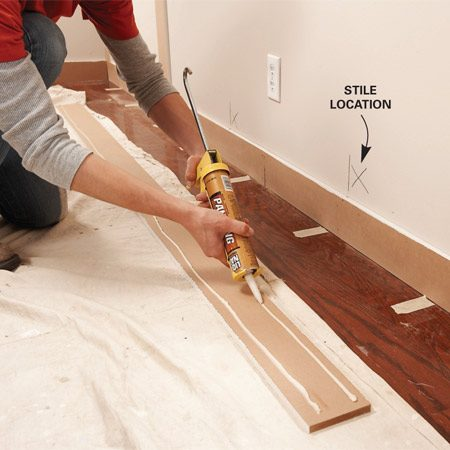 <b>Photo 7: Fasten stiles with panel adhesive</b></br> Fasten the stiles without worrying about stud locations. Apply adhesive to the stiles and tack them to the drywall with brads. The brads hold them in place until the glue dries.