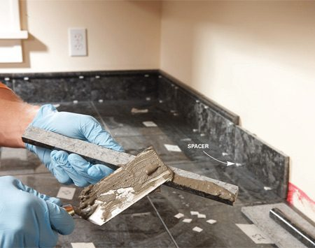 "<b>Photo 10: Add the backsplash</b></br> ""Back butter"" the backsplash and cap pieces to minimize the mess on the wall. Support backsplash tiles with spacers to leave a 1/8-in. gap for caulk."