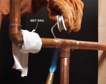 <b>Damp rag protects joints</b></br> Wet and wring out a 2-in.-wide strip of cloth and wrap it around the fitting you want to protect. The wet rag absorbs the heat and prevents the solder in the existing joint from melting.