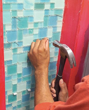 <b>Photo 6: Space and support tiles</b></br> Support sagging mosaic tiles with shims and/or nails until the adhesive sets. Tamp all the tiles level as we show in Photo 11.