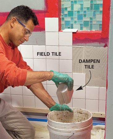 <b>Photo 8: Dampen and set field tile</b></br> Spread thin-set up to the horizontal layout line and around one corner of the alcove. Set those tiles and then continue tiling the wall, leaving out the row of tiles directly behind the shelf.