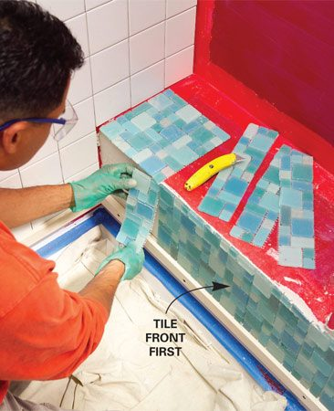 <b>Photo 10: Start at the front</b></br> Tile the front of the bench first. Cut the mosaic tiles into strips if you need to adjust the spacing to get a better fit with less cutting.