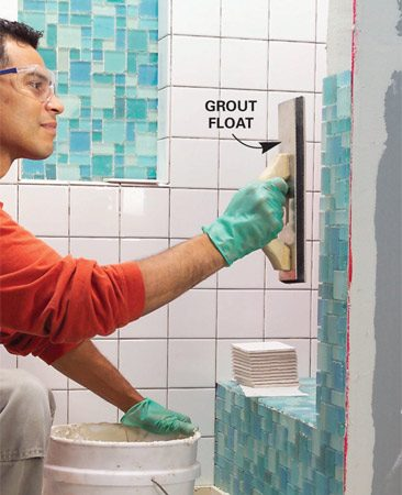 <b>Photo 11: Set tiles flat</b></br> Tile the bench and the end of the short wall. Force mosaic tiles evenly into the thin-set with a grout float.