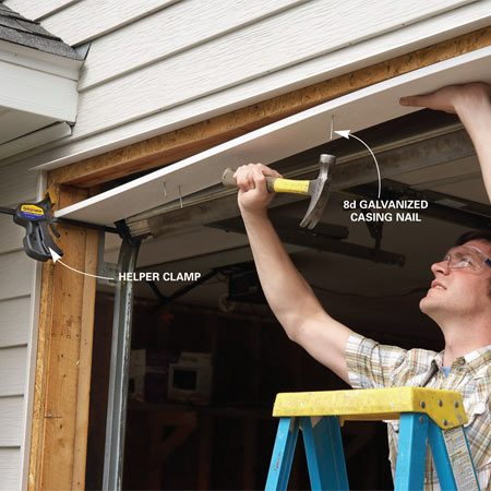 <b>Photo 2: Install the new jamb</b></br> Use a clamp to hold up one end of the top jamb, then nail the jamb to the framing with 8d galvanized casing nails.