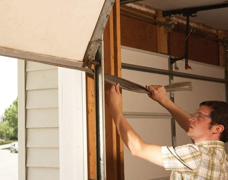<b>Photo 1: Remove the old garage door seal</b></br> <p>Lift the <strong>garage door</strong> to about 6 ft. high and  pull the old weather <strong>seal</strong> out through   the gap behind the door track. </p>