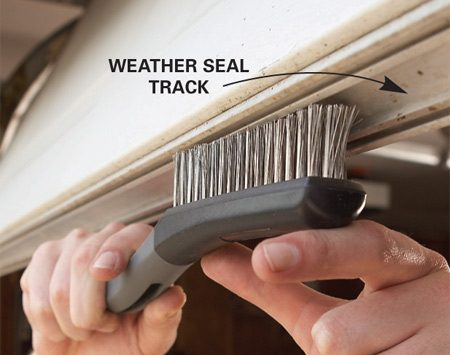 <b>Photo 2: Clean the track</b></br> <p>Scrape dirt and corrosion out of the <strong>garage door</strong>   weather<strong> seal </strong>track with a screwdriver   and a stiff brush. </p>