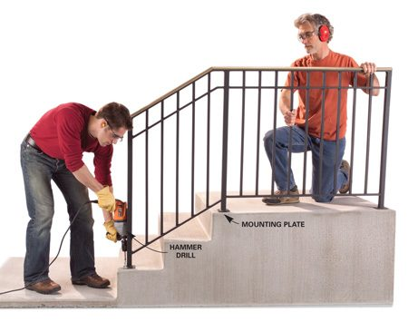 <b>Photo 5: Position the railing</b></br> Position the railing, making sure all the plates are an equal distance from the edges of the steps. Drill one hole at each end and drop in anchors to hold the railing in place. Then mark the remaining holes by drilling 1/2-in.-deep starter holes.