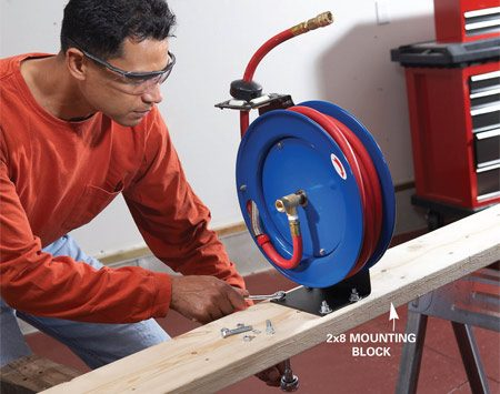 <b>Photo 1: Mount the reel</b></br> Predrill the ceiling-mounting holes and hose reel–mounting holes in the 2x8. Bolt the hose reel to the 2x8.
