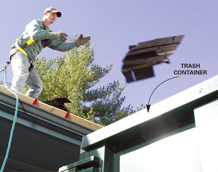 <b>Photo 5: Toss directly into trash</b></br> Throw old shingles directly into the trash container as they pile up at the roof jacks. Dispose of the shingles before the pile gets too large and they slide off the roof.