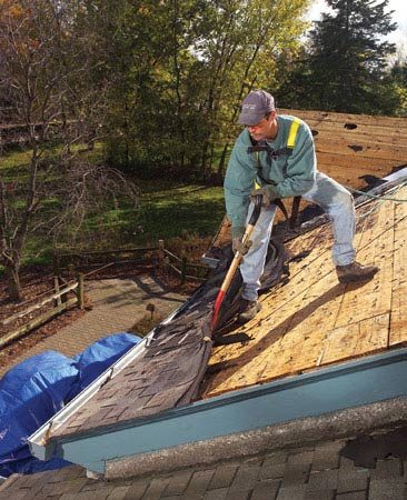 <b>Photo 8: Strip the roof edges</b></br> Remove the roof jacks and work the shingles loose along the roof edge with a fork. Then pull them off by hand.