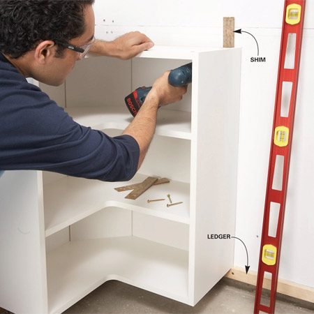 <b>Photo 2: Mount the cabinets</b></br> Set each cabinet on the ledger and screw it to studs. Hold a level against the front of the cabinet and level it with shims.