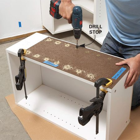 <b>Photo 3: Drill shelf support holes</b></br> Drill shelf-support holes in the outsides of any cabinets that will support open shelves. Position the holes with a scrap of pegboard.