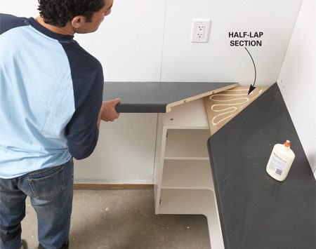 <b>Photo 7: Set the countertops</b></br> Spread glue on the half-lap joint and fit the mitered countertop sections together. Fasten the countertops by driving screws up through the cabinets.
