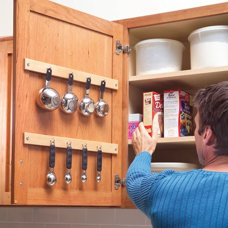 "<b>Hang items from cabinet doors</b></br> Don't let small stuff occupy valuable drawer and shelf space. Equipped with cup hooks, the backs of cabinet doors can hold measuring cups, spoons and other hanging items. With homemade racks, they can hold lids or spices. To see how to take advantage of your cabinet doors, go to <a href='http://www.familyhandyman.com'>familyhandyman.com</a> and search ""kitchen storage."" Be sure any protruding items will hang between shelves—or else the doors won't close."