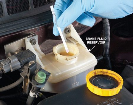 <b>Photo 1: Dip the strip</b></br> Dip the test strip into the brake fluid reservoir and wait for it to change color.