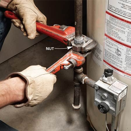 "<b>Photo 2: First disconnect the gas</b></br> Disconnect the gas at the ""union"" fitting. Place the larger wrench on the nut and hold the union's collar with another wrench. Start with the wrenches a quarter turn apart.</p>"