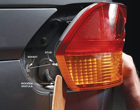 <b>Photo 2: Pry out the assembly</b></br> Pry the plastic stud out of the socket while pulling back on the taillight assembly.