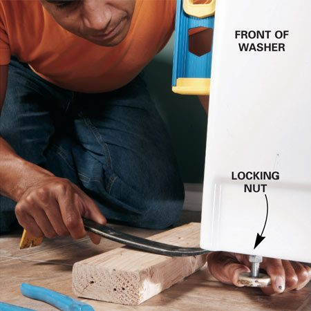 <b>Photo 1: Level the front</b></br> Lift the machine slightly with a pry bar to take the weight off the front legs, then turn the legs until the side of the washer is plumb.