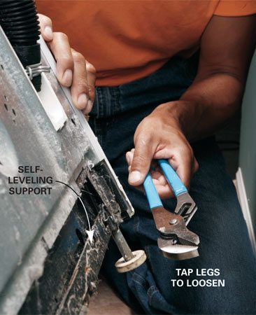 <b>Photo 3: Loosen the rear legs</b></br> If the rear leveling mechanism is frozen with rust, tap the legs a few times with a pliers or hammer to break it free.