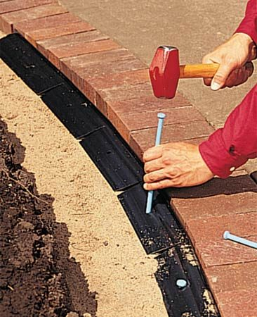 <b>Installing a border</b></br> To install a brick border, lay bricks on a compacted bed of gravel and sand. Lock them in place with plastic edging.
