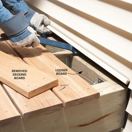 <b>Photo 1: Loosen the siding</b></br> Pry the siding away from the house and remove the deck board that's over the ledger to clear the way for new flashing.