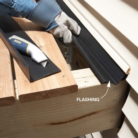 <b>Photo 2: Insert the flashing</b></br> Slide the flashing behind the siding so the lip covers the top of the ledger. Reattach the siding.