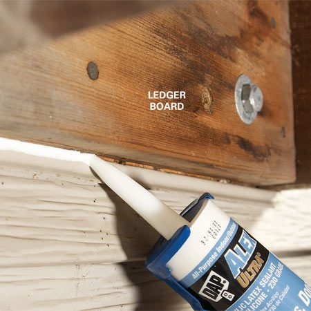 <b>Photo 3: Seal the bottom</b></br> Seal out water along the bottom edge of the ledger, if the bottom flashing is missing, by running a bead of caulk.