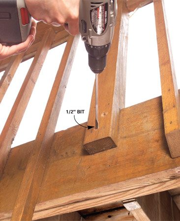<b>Drill bolt holes</b></br> Strengthen a loose railing post with carriage bolts. Drill a pair of holes through the post and framing. Angle the hole to avoid joist hangers.