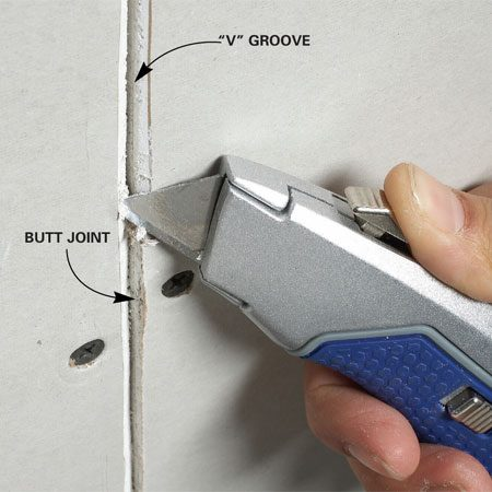 "<b>Cutting a ""V"" groove</b></br> Hold a utility knife at an angle and slice off the drywall edges to create the groove."