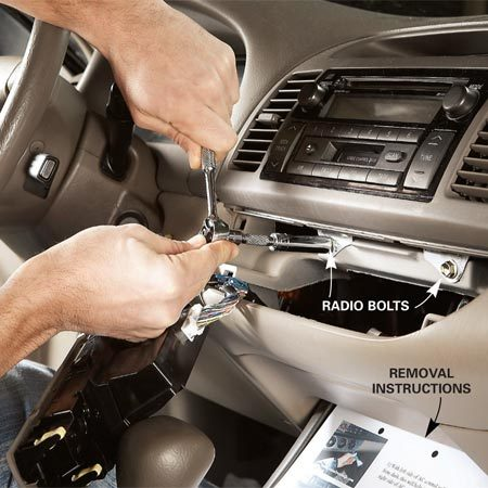 <b>Photo 2: Remove the trim panel and bolts</b></br> Pry out the radio trim panel to expose the radio fasteners. Then remove the retaining bolts.