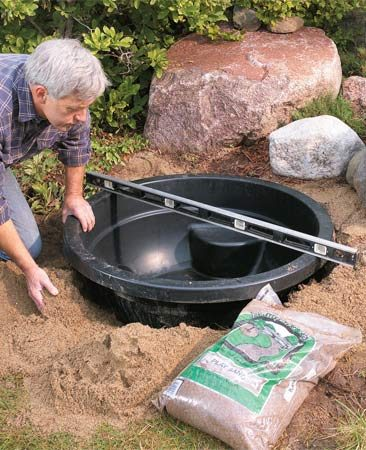 <b>Photo 1: Set the pond shell</b></br> Set the plastic pond in a hole with a few inches of tamped-down sand underneath. Backfill around the edges with additional sand.