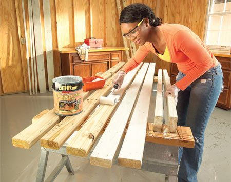 <b>Photo 4: Stain all parts</b></br> Stain the bench and trellis parts and the completed planter boxes before assembly to save time and mess.