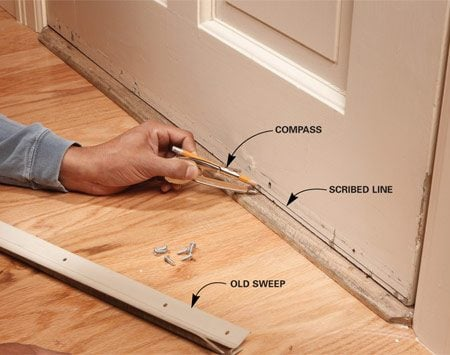 <b>Photo 1: Trim the door</b></br> Scribe a line on the door 3/8 in. above the top of the threshold. Remove the door and carefully cut along the line with a circular saw.