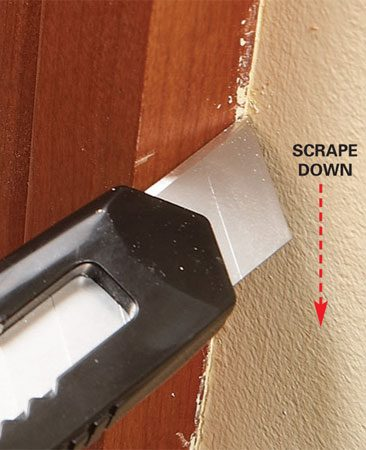 <b>Photo 2: Use a razor knife in corners</b></br> Scrape out corners and other tough spots with the edge of a razor knife. Angle it down as you scrape to avoid cutting the wood.