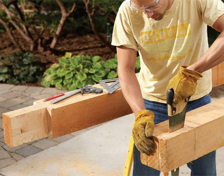 <b>Photo 1: Notch the beams</b></br> Notch the tops of the beams. Cut as deep as you can from both sides with a circular saw, then finish the cuts with a handsaw.
