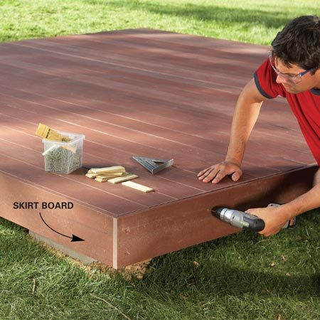 <b>Photo 8: Screw on the skirt board</b></br> Wrap the deck with skirt boards that match the decking, driving trim head screws just below the surface at the spacer locations (see Figure A).