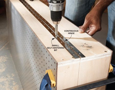 <b>Photo 3: Attach the hinge</b></br> Mount the door on the cabinet with a continuous hinge. Hold it in place with one screw on each end. Then use a small, self-centering bit to make pilot holes for the remaining screws.