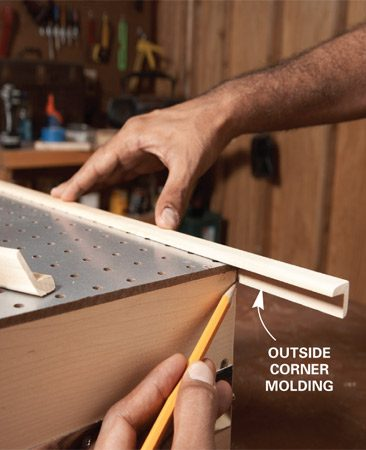 <b>Photo 4: Install trim</b></br> Trim the door with corner molding. Mark the inside of the molding at cabinet corners and turn the molding face down on the miter saw to cut the miter.