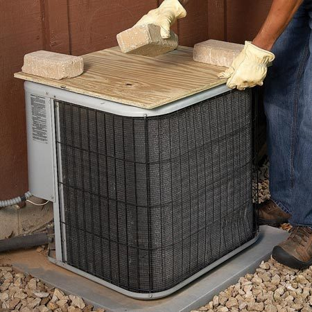 <b>Plywood cover</b></br> Plywood weighted down with bricks does a good job of protecting your air conditioner condenser in winter.