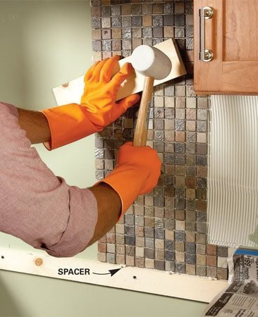 <b>Photo 3: Set the tile</b></br> Tap the tile into the mastic with a wood scrap and a rubber mallet. Stand back, look at the tiles and straighten any crooked ones.