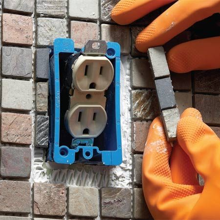 <b>Photo 4: Saw tiles for exact fits</b></br> Cut tile sheets to the nearest full row to fit around outlets, then fill the gaps with tiles cut on a wet saw.