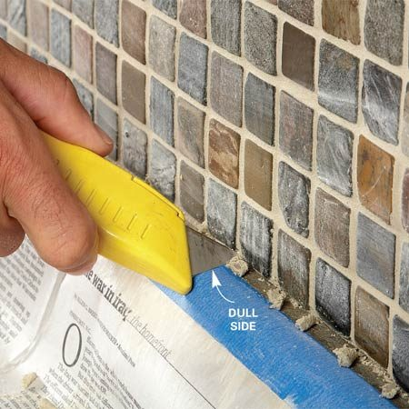 <b>Photo 6: Scrape out corners</b></br> Rake the grout out of the joints at inside corners and along the bottom with a utility knife so you can fill them with caulk. Keep the dull side of the blade along the countertop.