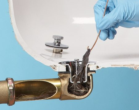 Photo 2: Hook clogged hair with a bent wire and<br/> pull it out.