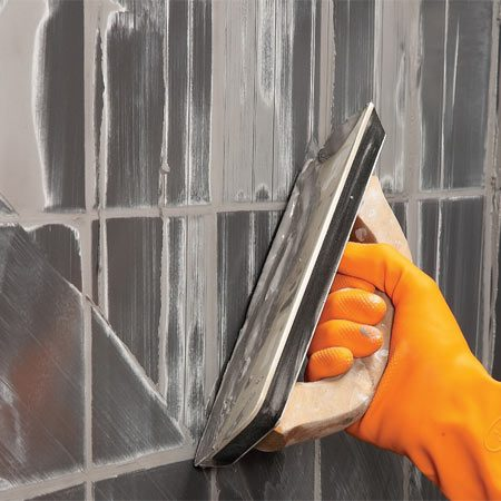 <b>Hold grout float at 45-degrees </b></br> Fill the joints by pushing the grout at an angle to the joints with a grout float. Start in one corner and work methodically to fill all the joints.