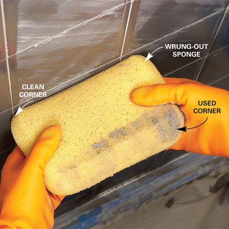 <b>Remove excess grout with a sponge</b></br> Remove grout from the face of the tile with the corner of a damp sponge. Swipe from bottom to top, using a clean corner of the sponge for each stroke.