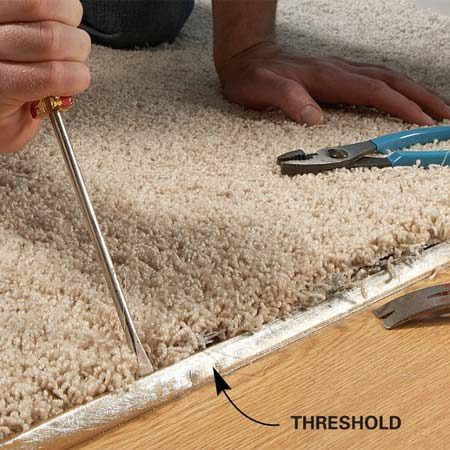 <b>Photo 1: Release the carpet</b></br> Bend open the threshold's lip to release the carpet. Be careful not to snag the carpet as you push the screwdriver under the lip.