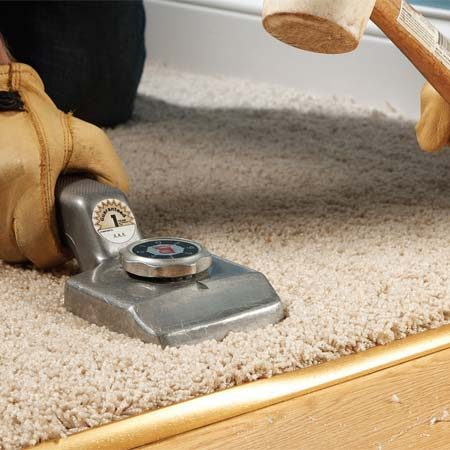 <b>Photo 4: Lock the carpet down</b></br> Drive down the lip, tapping gradually back and forth along its entire length. On the final pass, pound hard to lock the carpet into the threshold.